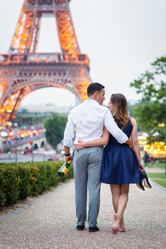 Summer engagement photos in Paris - Engaged couple walking towards the Eiffel Tower with shoes and champagne in hand