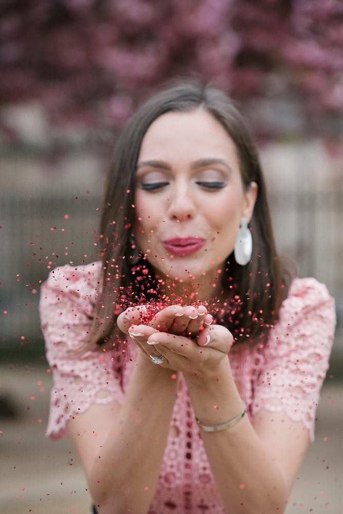 Couples portrait ideas - Beautiful girl blowing into colorful confettis in front of cherry blossoms
