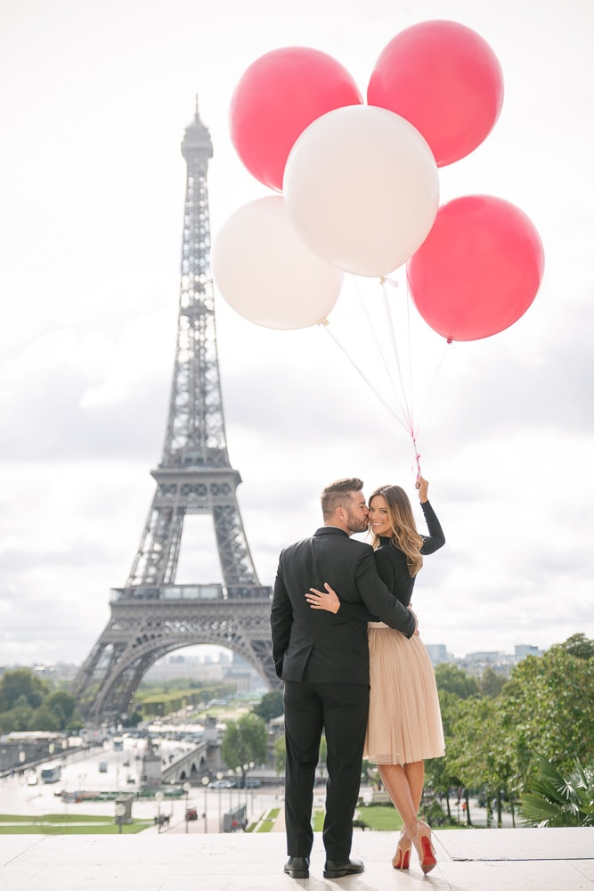 Gentleman kissing his fiancée on the cheek in front of the Eiffel Tower