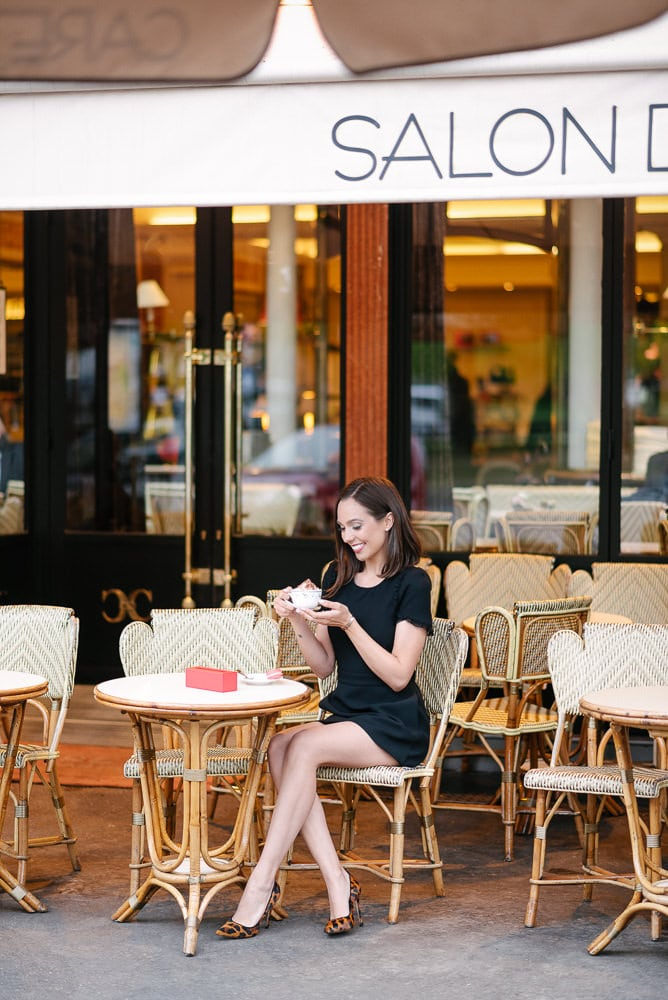 Posing ideas for portraits - Beautiful girl sitting outside café Carette with cappuccino in her hands and smiling